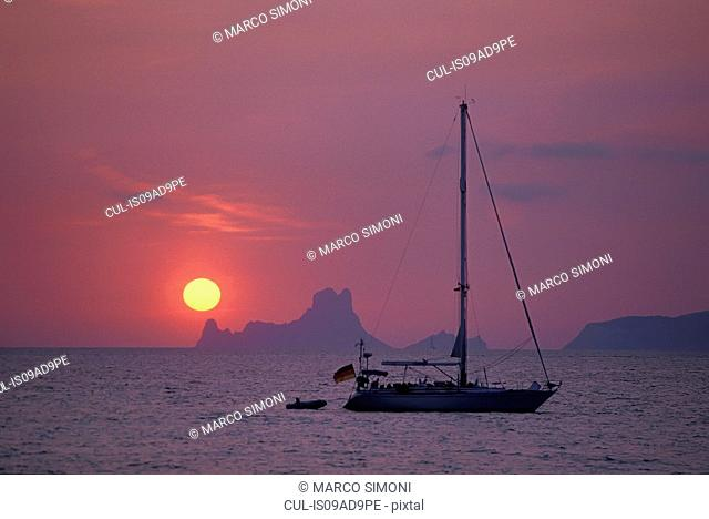Boat at sunset against background of Es Vedra, Formentera, Balearic Islands, Spain
