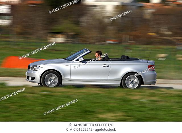 BMW 120i Convertible, model year 2008-, silver, driving, side view, City, open top