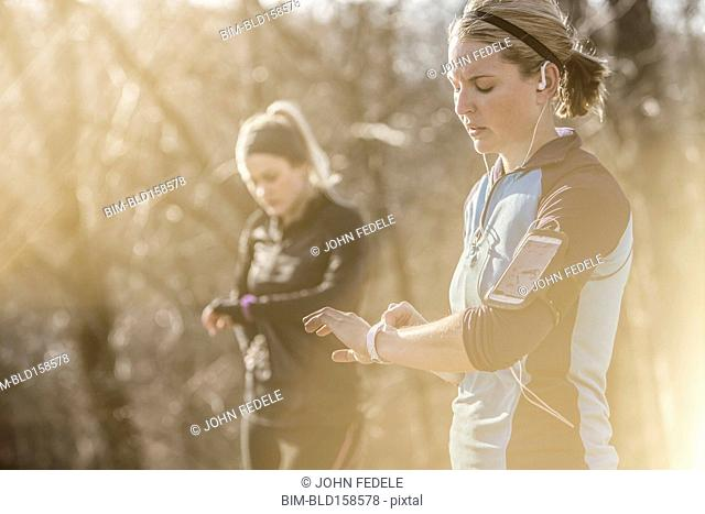 Caucasian runners checking fitness watches in forest