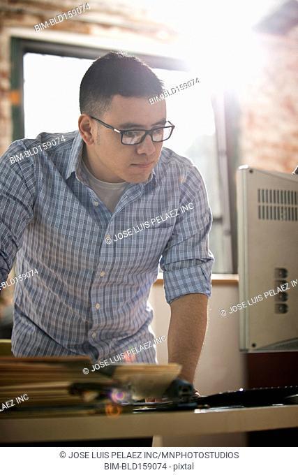 Hispanic businessman using computer at office desk