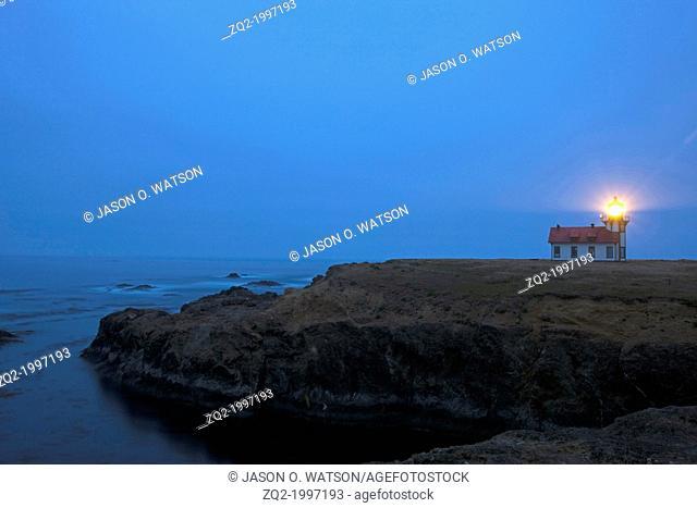 The Point Cabrillo lighthouse stands as a beacon at dusk along Mendocino cliffs near Mendocino, California, USA