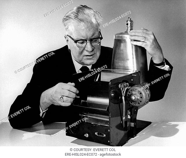 Chester Carlson 1906-1968 with the first model of his invention of 1938 that evolved over 20 years into the Xerox copier. Ca. 1960. BSLOC-2010-18-180