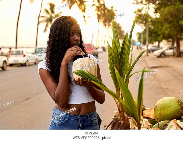 Mocambique, Maputo, portrait of young woman drinking coconut water on the street