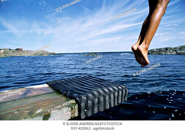 Boy jumping off dock. Matton. Sweden