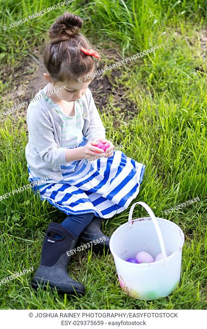 Easter egg hunt with young child hunting the eggs outdoors on a family property in Oregon