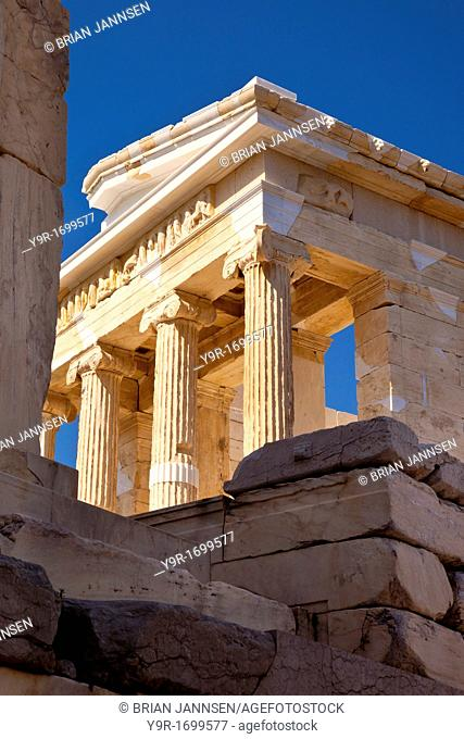 Stone ruins and the Temple of Athena Apteros Nike on the Acropolis, Athens Greece