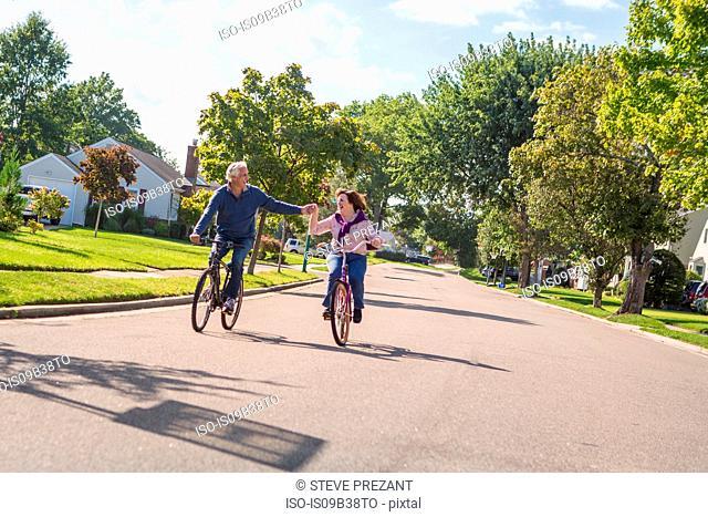 Romantic senior couple holding hands cycling along suburban road