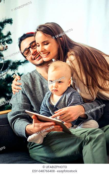 family finds a digital tablet in a gift on the Christmas night, near the wood stove and lit Christmas tree in their living room