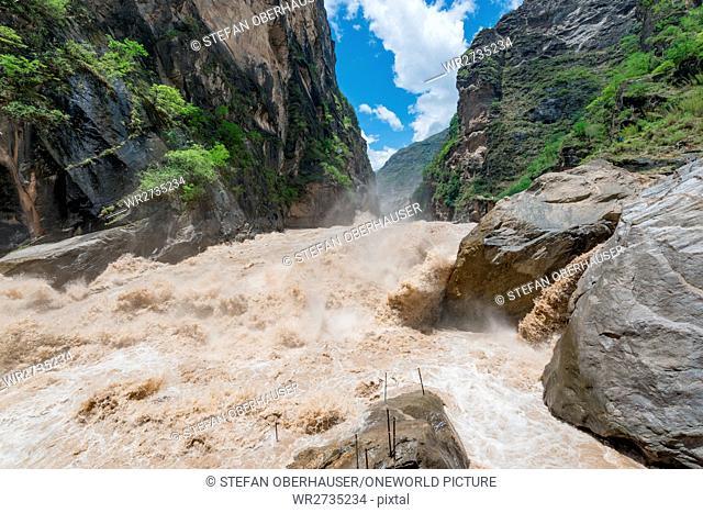 China, Yunnan Sheng, Diqing Zangzuzizhizhou, hike (2-day tour) to the Tigersprung Gorge of the Yangtze River, Wild Yangtze River under a blue cloudy sky