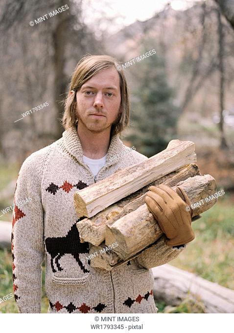 Young blond man carrying firewood