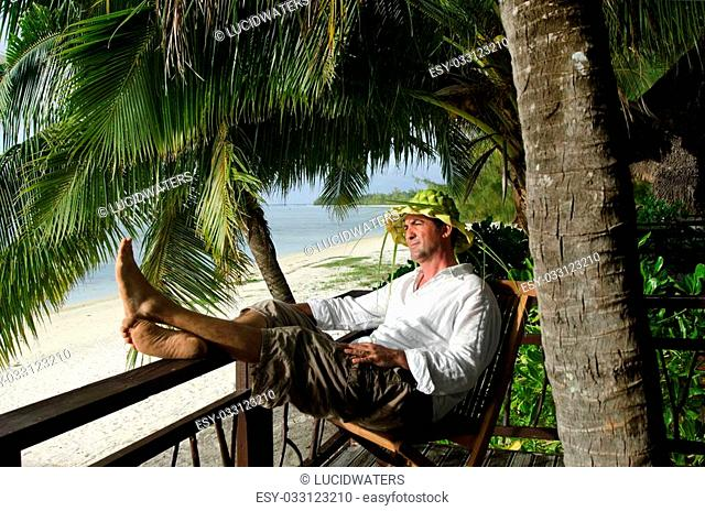 Successful man in his 40's relax during travel vacation on tropical island in Aitutaki lagoon, Cook Islands