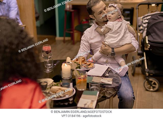 father with baby, Family eating in restaurant, Vegan Oriental, Kismet, in Munich, Germany