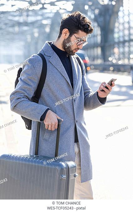 Businessman with baggage looking at cell phone