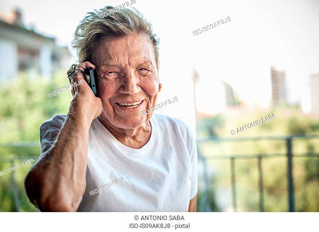 Portrait of a very senior woman chatting on smartphone on apartment balcony