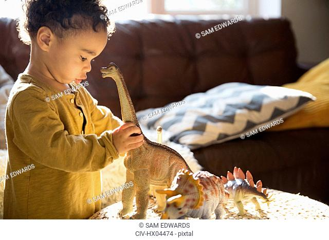 Innocent boy playing with dinosaur toys