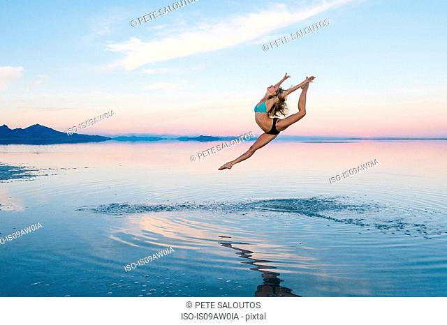 Female ballet dancer leaping mid air over lake, Bonneville Salt Flats, Utah, USA
