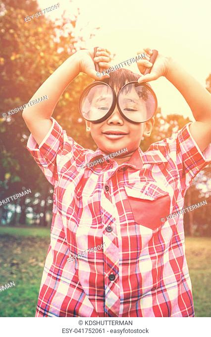 Playful asian child enjoying at park on vacation. Young smart boy peers at camera through two magnifying glass on blurred nature background