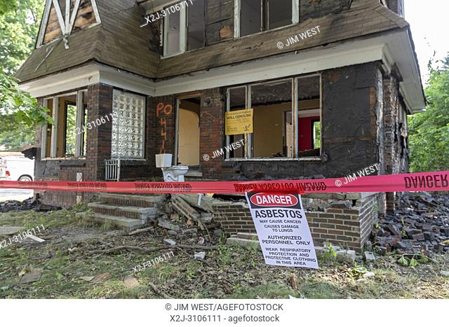 Detroit, Michigan - A warning about asbestos exposure hangs outside an abandoned house being prepared for demolition. The property will be used for a new city...