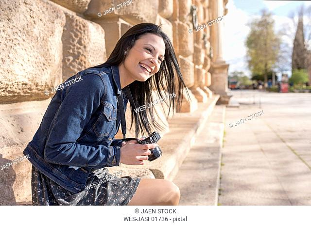 Spain, Granada, happy young woman with camera at the Alhambra