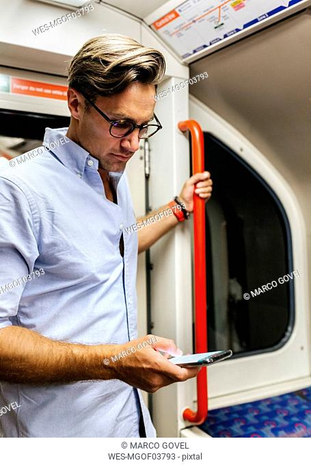 UK, London, businessman in underground train looking at cell phone