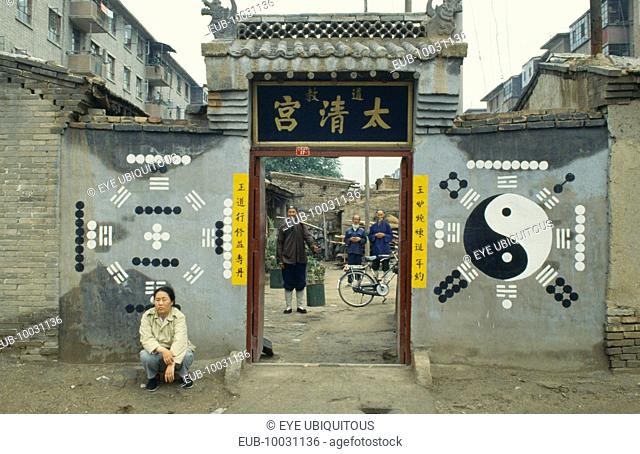 Monks or priests seen through the entrance of Daoist temple with trigram and yin yang symbols on the exterior walls and person crouched outside