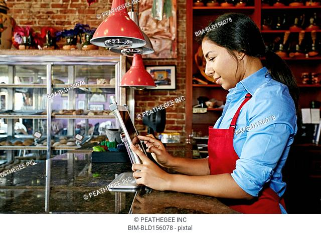 Hispanic cashier using digital tablet register in bakery