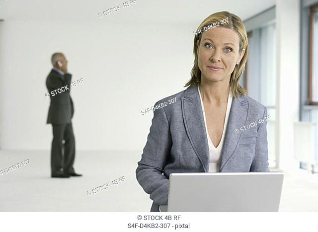 Blond businesswoman working on a laptop, elderly manager phoning in the background