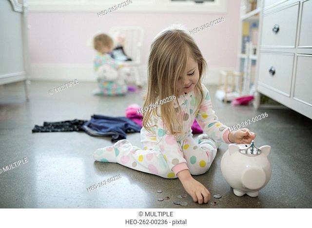 Girl placing coins in piggy bank bedroom floor