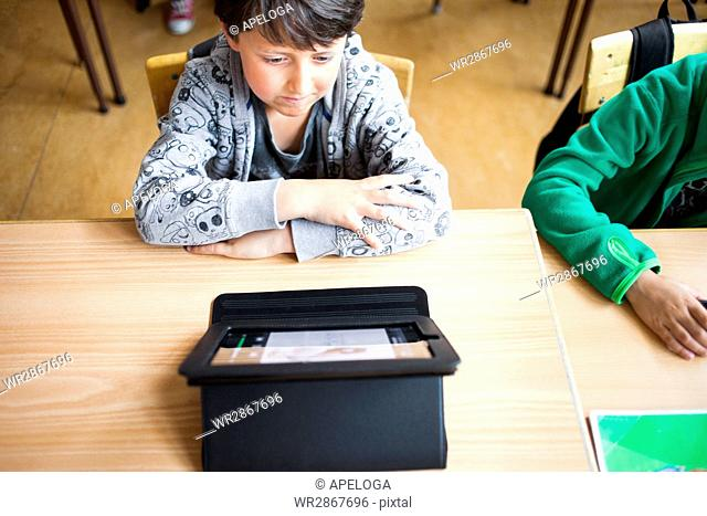 High angle view of schoolboy using digital tablet at desk