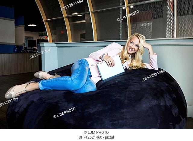 Business portrait of a beautiful young millennial businesswoman with long blond hair holding a tablet and posing for the camera on a beanbag chair in the...