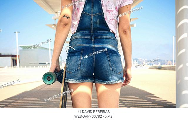 Back view of young woman with longboard on beach promenade, partial view