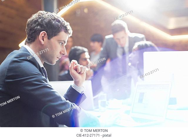 Serious businessman working at laptop in office