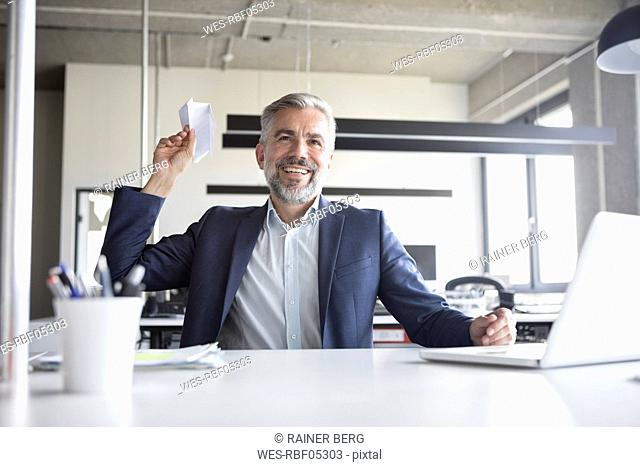 Happy businessman throwing paper plane in office