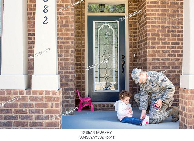 Male soldier putting on daughter's shoes at front door at air force military base