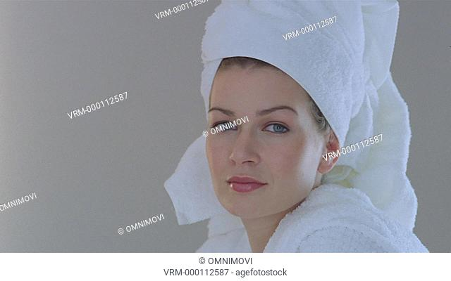 Young woman wrapped in a towel, turning to smile at camera