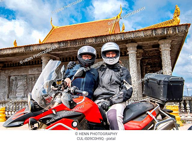 Bikers posing on ADV motorbike in front of buddhist temple, Phnom Penh, Cambodia