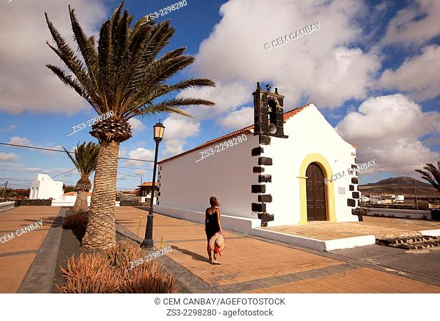 Woman posing in front of the Ermita de San Antonio de Padua parish church, Lajares, Fuerteventura, Canary Islands, Spain, Europe