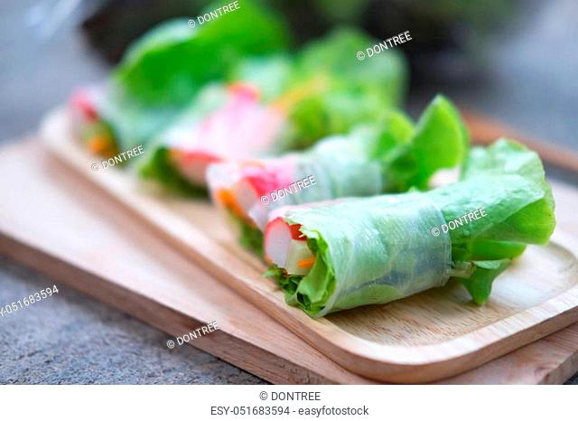 Vegetable salad roll on wood tray, healthy food. Selective focus