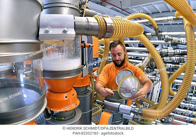An employee oversees a cast extrusion machine for manufacturing stretch foil, in the factory of plastics manufacturer POLIFILM in Weissandt-Goelzau, Germany