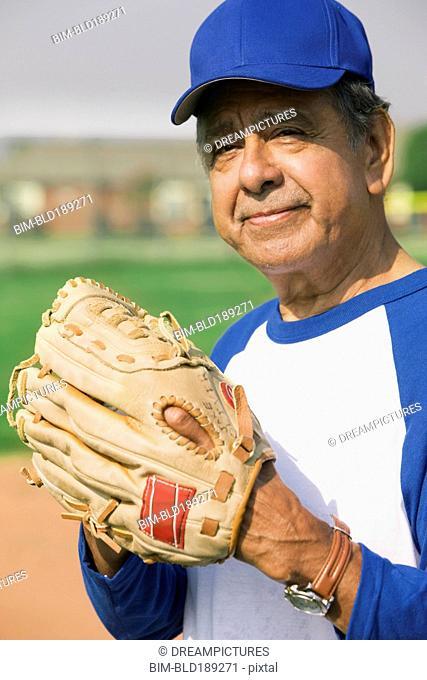 Senior Hispanic man playing on baseball team