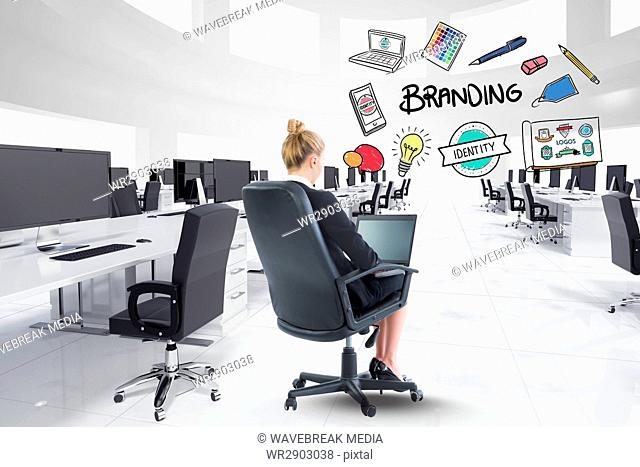 Digital composite image of businesswoman using laptop with branding text and icons in office