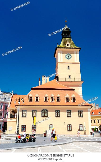 Brasov, Transylvania, Romania, 6th July 2015: Brasov Council Square is historical center of city, people sitting and walkinng near old Town Hall
