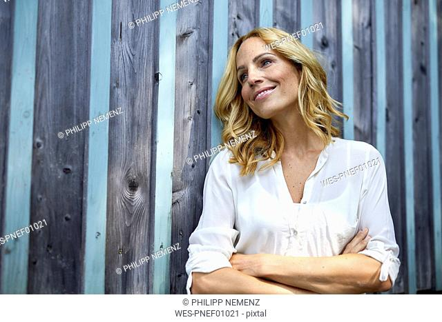 Smiling blond woman in front of wooden wall