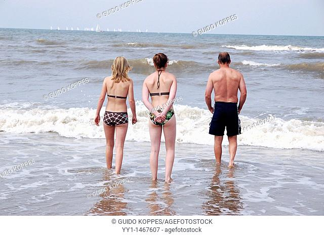 Scheveningen, Netherlands. Three people in swimsuits walking into the salty water of the North Sea for a swim
