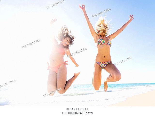 Female friends jumping on beach