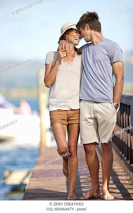 Young couple walking along jetty, arms around each other