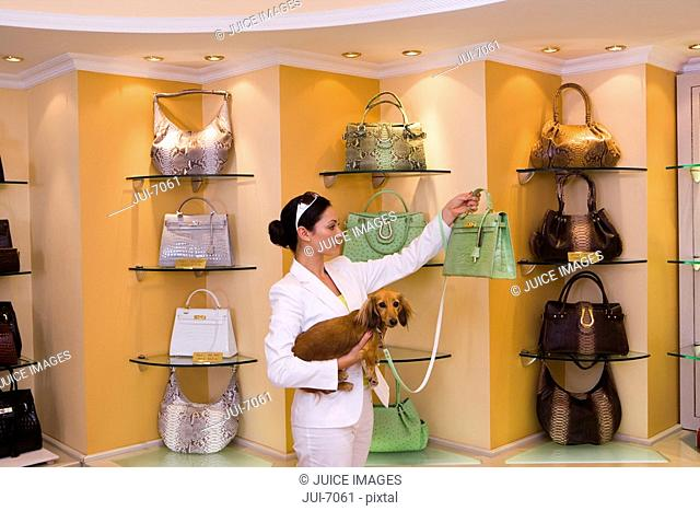 Young woman looking at green designer handbag in glamorous boutique, carrying dog, side view
