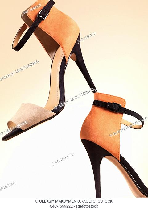 Artistic still life of a pair of fancy open-toe high heel shoes isolated on beige background