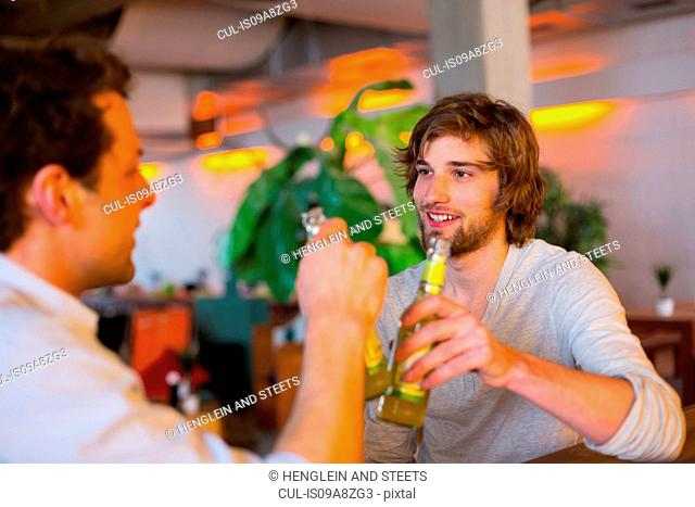 Two men with bottles of beer
