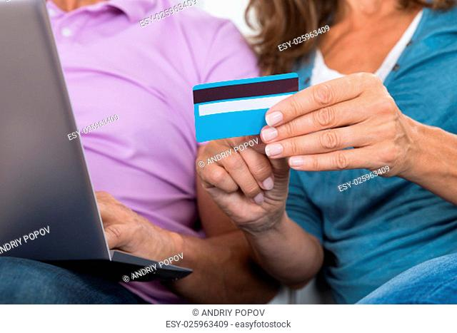 Close-up Of Couple Holding Laptop And Credit Card